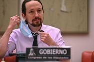 Pablo Iglesias se retira la mascarilla antes de intervenir en la comisión de Derechos Sociales del Congreso.