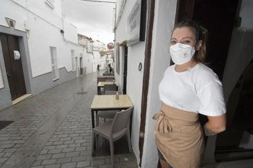 Una camarera con mascarilla espera clientes en un bar completamente vacío de Conil de la Frontera.