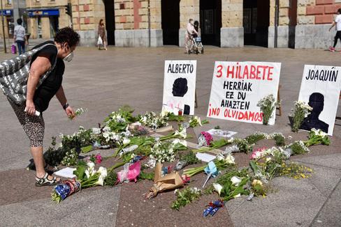 Una mujer coloca flores frente al consistorio de Eibar (Guipúzcoa), en memoria de los dos desaparecidos en Zalbibar.