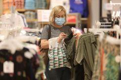 Una mujer con mascarilla compra en un centro comercial.