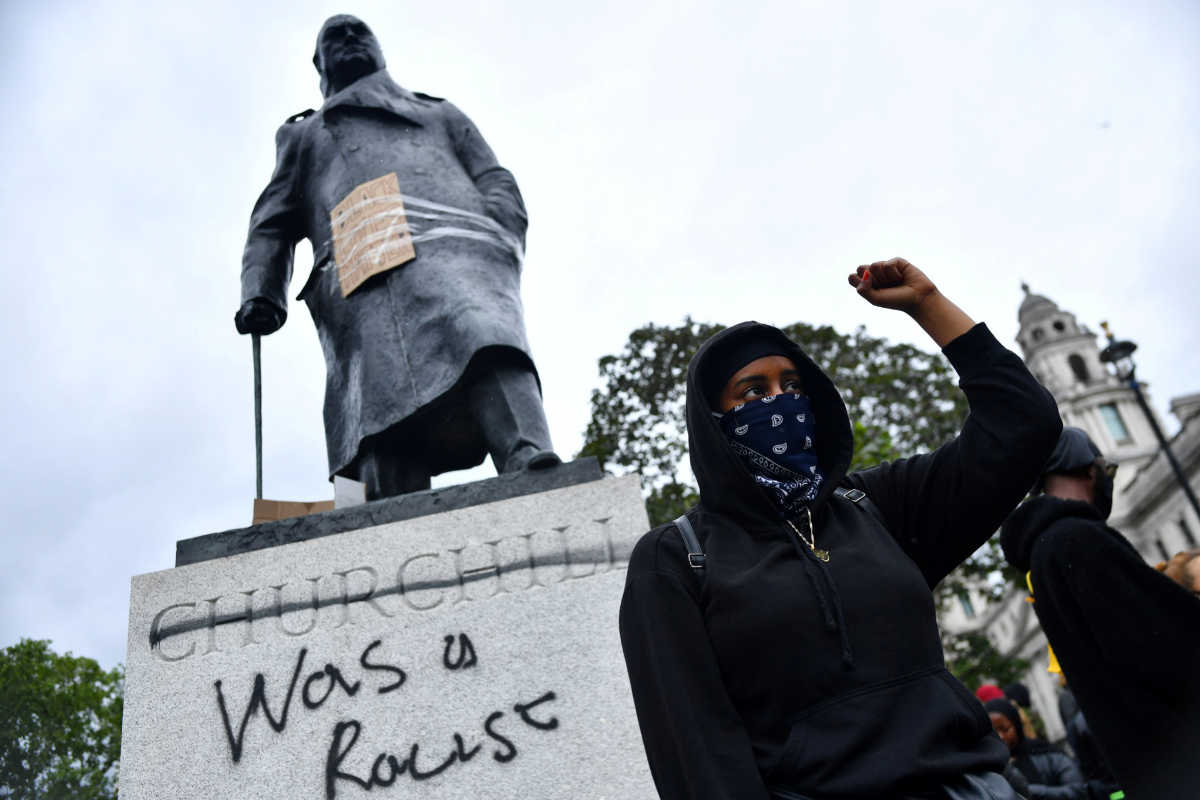 Un manifestante, bajo la estatua de Churchill con la pintada 'Fue un racista', el domingo en Londres.