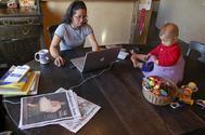 Una madre vigila a su hijo mientras trabaja desde casa.