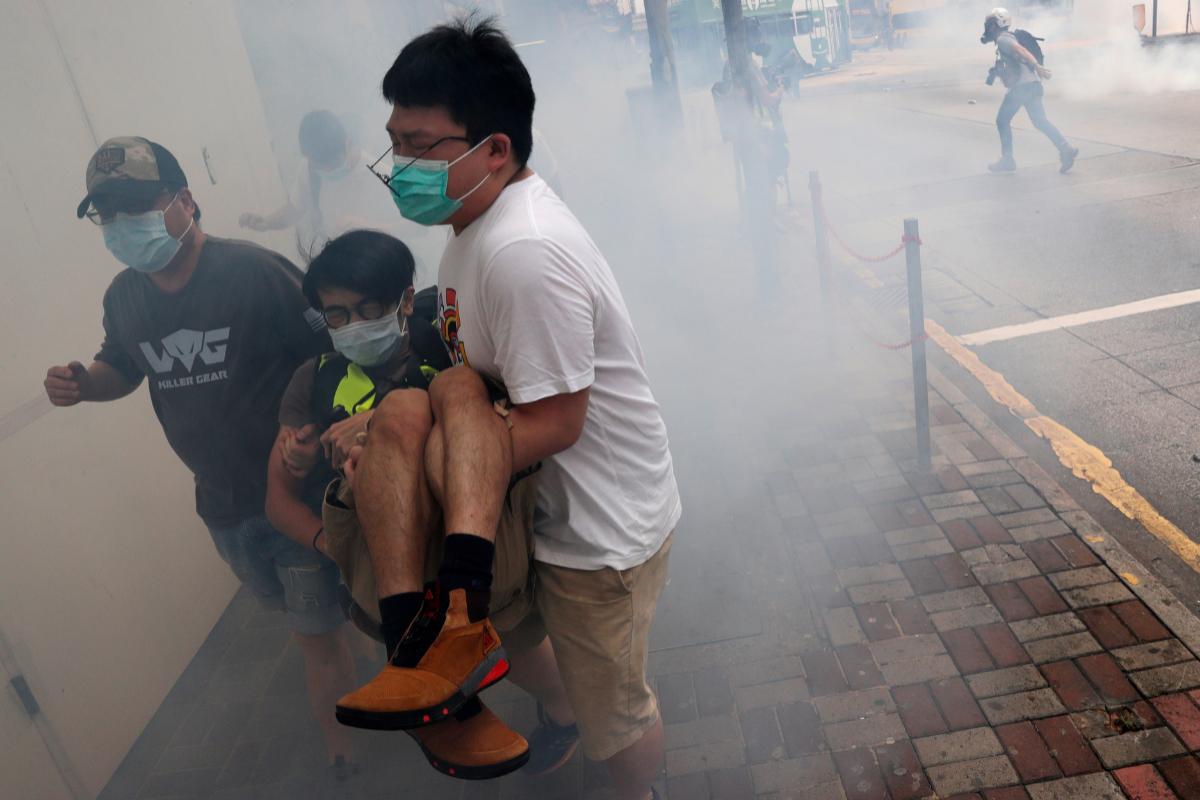 Manifestantes huyen del gas lacrimógeno lanzado por la policía durante una protesta contra la nueva ley de seguridad.