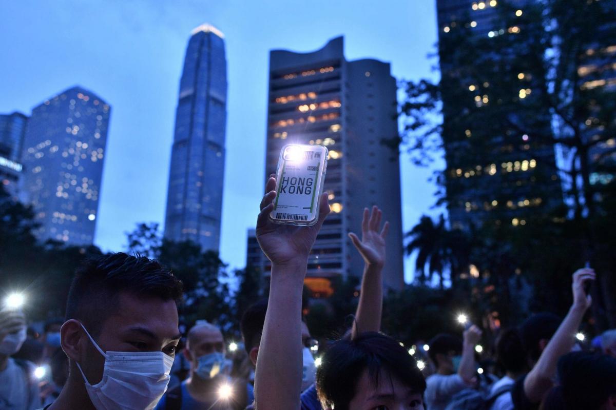 Manifestantes levantan sus teléfonos con la linterna encendida, en el centro de Hong Kong, en el aniversario de las protestas de 2019.