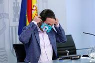 El vicepresidente del Gobierno, Pablo Iglesias, se coloca la mascarilla tras terminar la rueda de prensa, este martes, después del Consejo de Ministros.