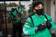 Mototaxistas de Yakarta se colocan sus mochilas protectoras.