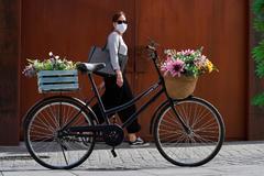 Una mujer con mascarilla pasa junto a una bicicleta en una calle de Ávila.