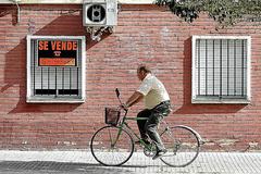Un hombre pasa por delante de un piso en venta en la barriada sevillana de La Juncal.
