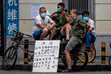 Varios obreros de la construcción aguardan en la calle junto a un cartel en el que ofrecen sus servicios en Cantón (China).