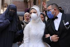 Unos novios celebran su boda con mascarilla en El Cairo.