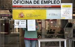 Una funcionaria coloca carteles de atención al público en una oficina de empleo.