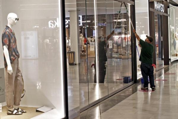 Un operario limpia el escaparate de una tienda durante la reapertura.