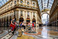 Mujeres desplazándose en bici por la galeria Vittorio Emanuele II de Milán