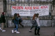 Varios estudiantes de la UPV en Vitoria caminan junto a una pancarta que anuncia unas jornadas sobre los presos de ETA.