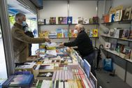 Un librero atiende a un cliente en la Feria del Libro de Santiago.