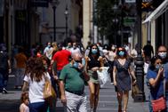 Gente protegida con mascarilla pasea por los comercios de las calles del centro de Córdoba este sábado.