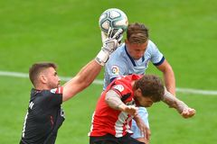 Unai Simón detiene un balón ante Marcos Llorente.