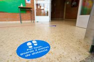 Carteles para guardar la distancia en un colegio de Torrejón de Ardoz (Madrid).