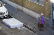 Una mujer pasa frente a un colchón abandonado.