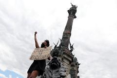 Manifestante protestando contra la estatua de Colón en Barcelona.