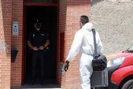 Un agente de Policía llega al edificio de Úbeda (Jaén) donde se produjo el triple asesinato.