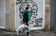 Una personas camina delante de una tienda cerrada en Madrid.
