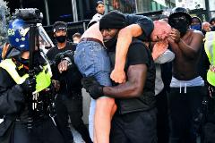 Patrick Hutchinson carga a hombros con un manifestante blanco herido durante una protesta en Londres este sábado.
