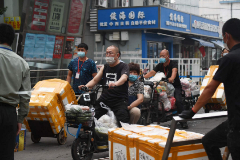 People carry goods out of the Jingshen lt;HIT gt;seafood lt;/HIT gt; lt;HIT gt;market lt;/HIT gt; in Beijing on June 13, 2020. - The lt;HIT gt;market lt;/HIT gt; was closed for disinfection and investigation on June 12 after it was found that a newly identified coronavirus patient had visited it. (Photo by GREG BAKER / AFP)