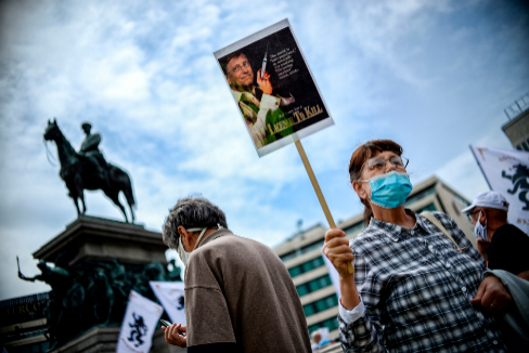 """Una manifestante con un cartel de Bill Gates y la leyenda """"Licencia para matar"""""""