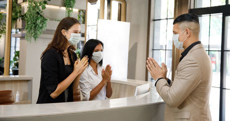 Recepcionistas con mascarilla en un hotel asiático.