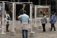 Paseantes observan algunas de las obras instaladas en el Arenal de Bilbao.