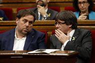 El ex presidente catalán Carles Puigdemont (dcha.) habla con Oriol Junqueras, en 2017, en el Parlament.