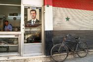 FILE PHOTO: A picture of Syrian President Bashar al- lt;HIT gt;Assad lt;/HIT gt; is seen on a door of a butcher shop, during a lockdown to prevent the spread of the coronavirus disease (COVID-19), in Damascus