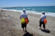 Dos de los auxiliares de playa de la Junta en la playa de El Zapillo en Almería.