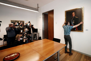 Un empleado del Parlamento de Navarra retira el cuadro de Juan Carlos I de la sala de gobierno.
