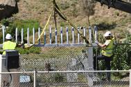 Dos operarios instalan los nuevos elementos que sustituyen a las concertinas en la valla de Ceuta.