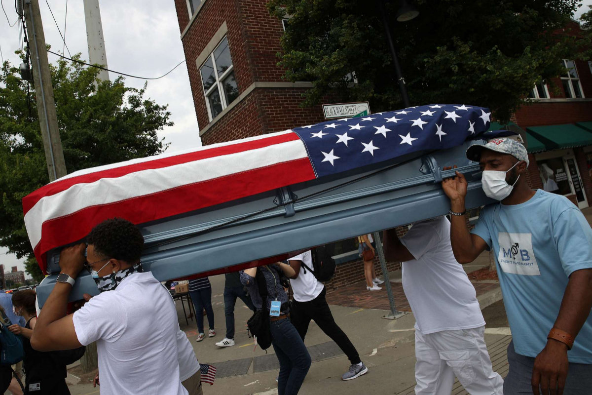 Varias personas cargan un ataúd vacío simbólico con la bandera de EEUU, en Tulsa, Oklahoma.