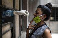 Un sanitario hace el test de coronavirus a una mujer en una escuela de Nueva Delhi (India)
