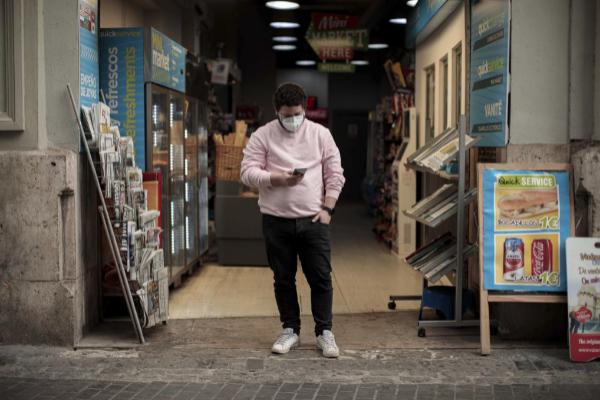 Un hombre consulta su teléfono móvil delante de un kiosko, en Valencia.