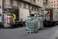 Varios trabajadores descargan camiones ante un negocio, en Valencia.