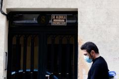 Un hombre camina por delante de un inmueble con un cartel de alquiler.