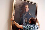 """Un empleado del Parlamento retira de la """"sala de gobierno"""" el retrato de Juan Carlos I."""