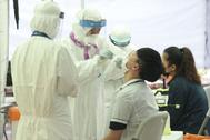 Trabajadores sanitarios toman muestras para realizar tests de Covid-19 a estudiantes, en Seúl.
