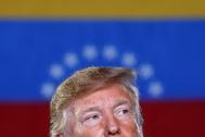 Donald Trump, con la bandera de Venezuela de fondo.