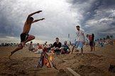 Unos jóvenes saltan la hoguera en la playa de La Malvarrosa, en Valencia.