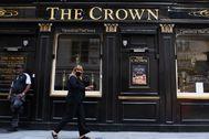 Una mujer camina delante de un pub cerrado.