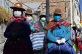 Varias mujeres con el traje típico peruano y con mascarillas.