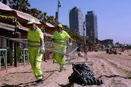 GRAF6221. lt;HIT gt;BARCELONA lt;/HIT gt;.- Trabajadores municipales retiran las vallas con las que se han cerrado los accesos a la playa de la Barceloneta que ha permanecido cerrada toda la noche para evitar concentraciones con motivo de la verbena.