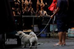 Un hombre habla con un vendedor de carne de perro en Yulin, en 2018.