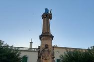 Estatua de Fray Junípero Serra, con una bolsa en la cabeza y una botella en la mano, en Petra (Mallorca).